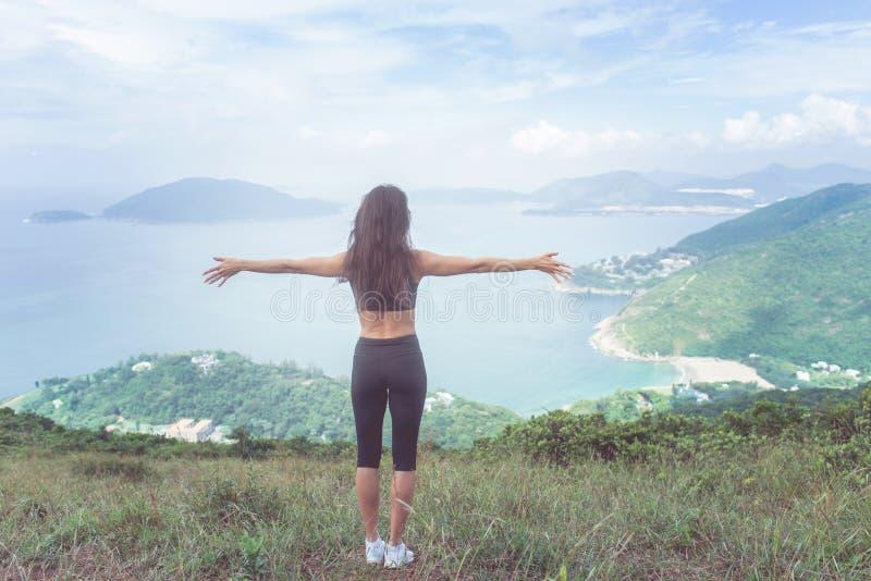 Punto di vista posteriore della donna di forma fisica che sta sulla montagna verde con lei espressione di sguardo stesa del paesa fotografie stock libere da diritti