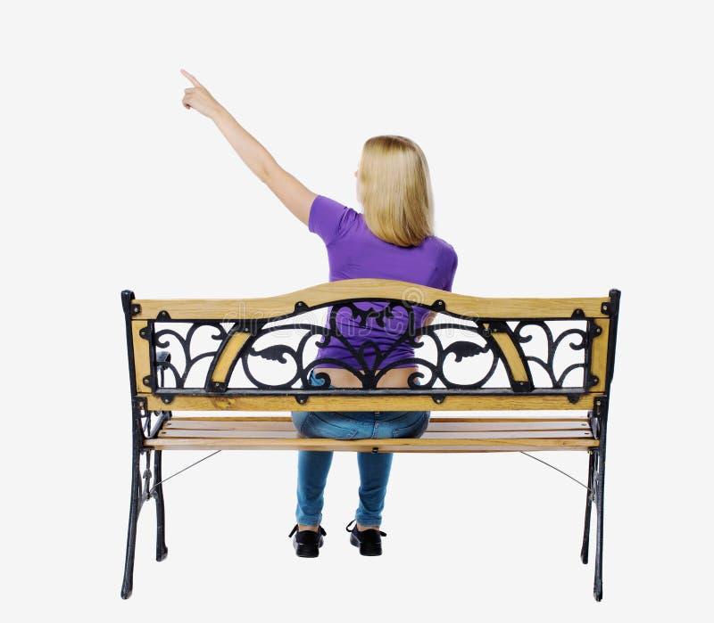 Punto di vista posteriore della donna indicante che si siede su un banco fotografie stock