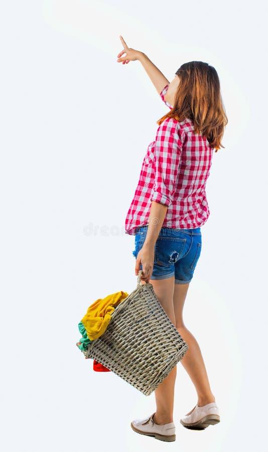 Punto di vista posteriore della donna indicante con la lavanderia sporca del canestro la ragazza è impegnata nel lavaggio immagine stock libera da diritti