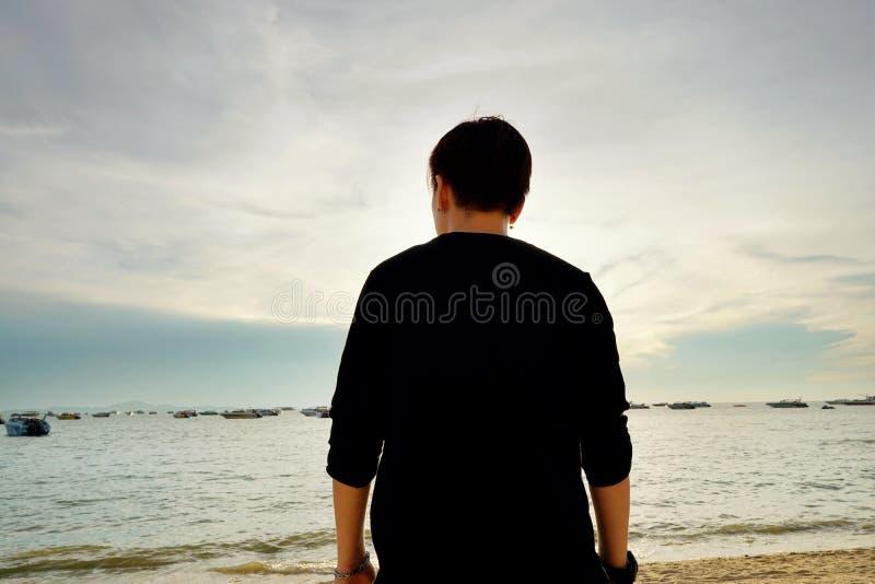 Punto di vista posteriore della donna nella spiaggia al tramonto immagine stock libera da diritti