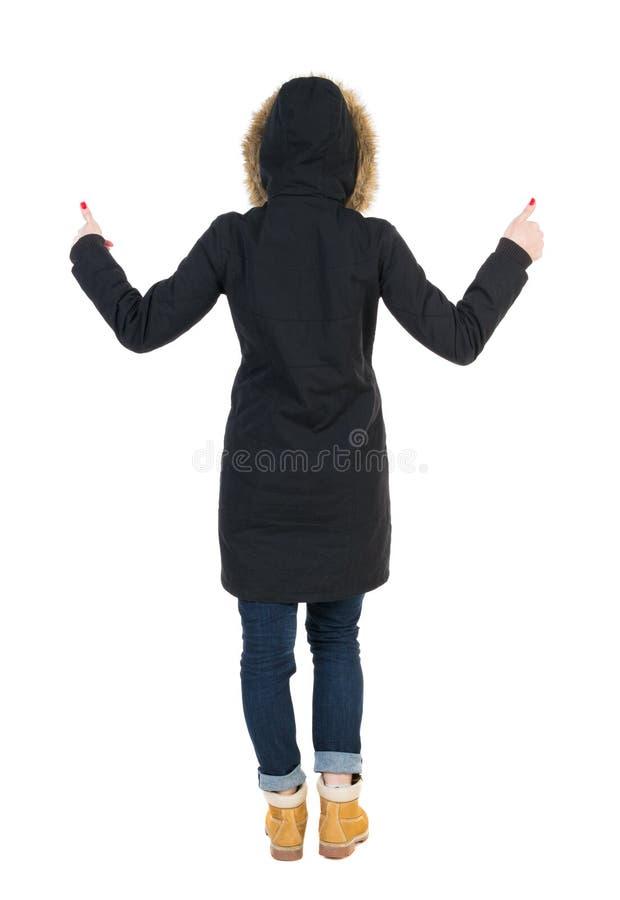 Punto di vista posteriore della donna in pollici del parka su fotografie stock