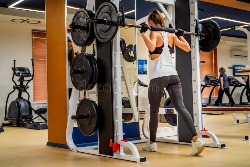 Punto di vista posteriore della donna sportiva che fa gli edifici occupati sulla macchina del fabbro in palestra fotografie stock libere da diritti