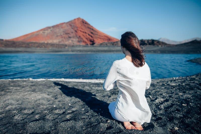 Punto di vista posteriore della donna in vestiti bianchi che prega in spiaggia di sabbia nera fotografia stock
