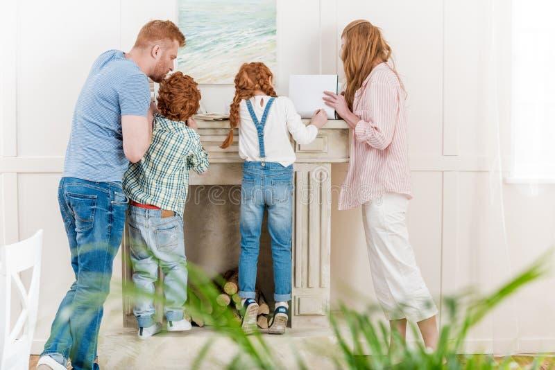 Punto di vista posteriore della famiglia della testarossa con due bambini che stanno insieme vicino al camino e che leggono le ri immagine stock