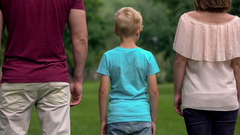 Punto di vista posteriore della famiglia felice che guarda in avanti, raggiungente insieme gli scopi, motivazione fotografia stock