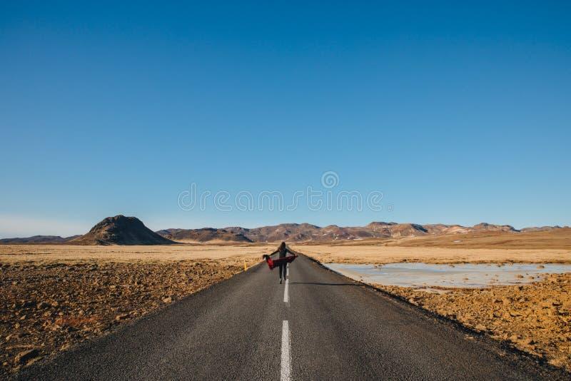 punto di vista posteriore della giovane donna che cammina in strada asfaltata in Islanda, reykjanes immagini stock