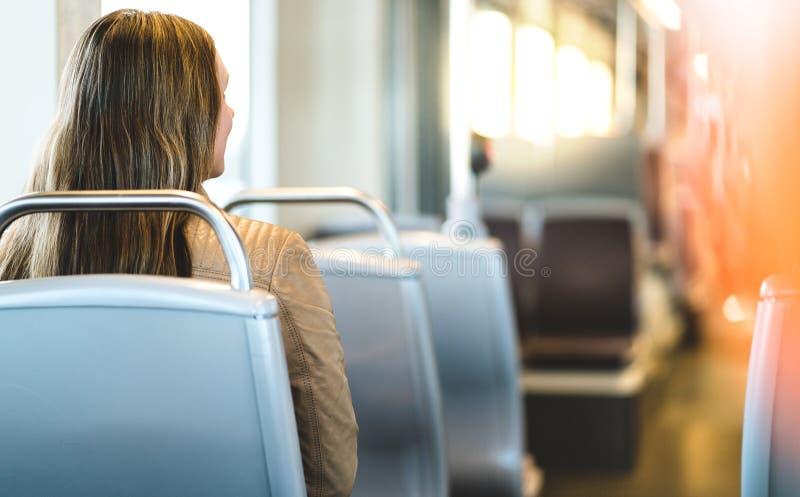 Punto di vista posteriore della giovane donna che si siede in trasporto pubblico immagini stock