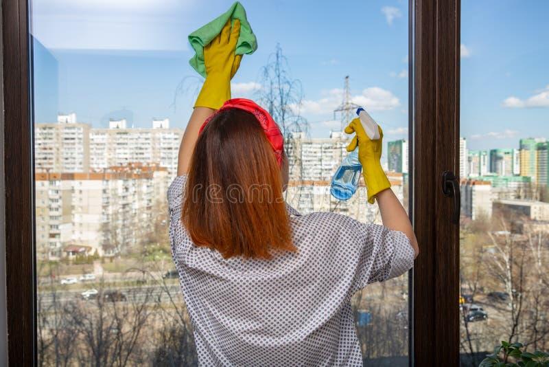 Punto di vista posteriore della governante irriconoscibile che pulisce finestra panoramica con l'aiuto del pulitore di vetro e de immagini stock