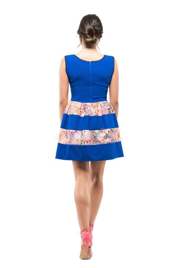 Punto di vista posteriore della parte della giovane donna nell'allontanarsi blu del vestito da short di estate fotografia stock