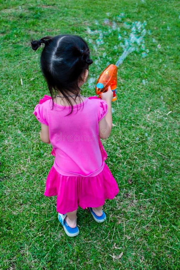 Punto di vista posteriore della ragazza adorabile asiatica che gioca sull'erba verde esterno immagine stock