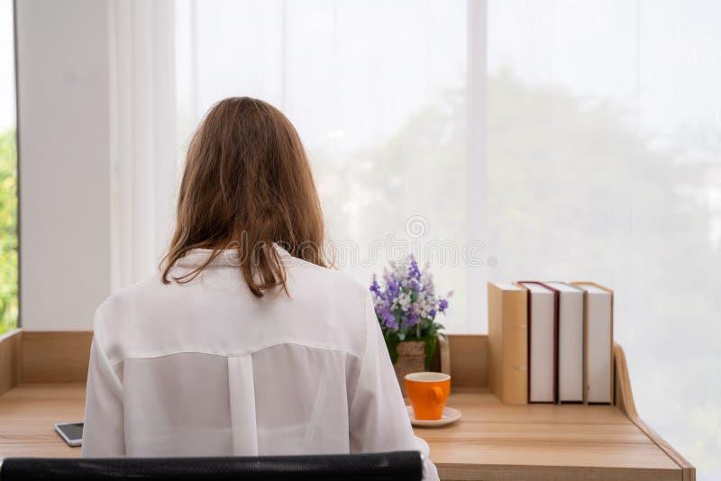 Punto di vista posteriore della ragazza dei pantaloni a vita bassa nel messaggio casuale dell'attrezzatura nella chiacchierata on fotografia stock