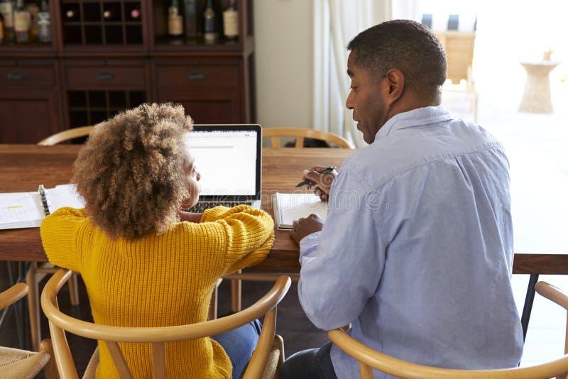 Punto di vista posteriore della ragazza pre-teen che si siede ad una tavola nella sala da pranzo che lavora ad un computer portat immagini stock libere da diritti
