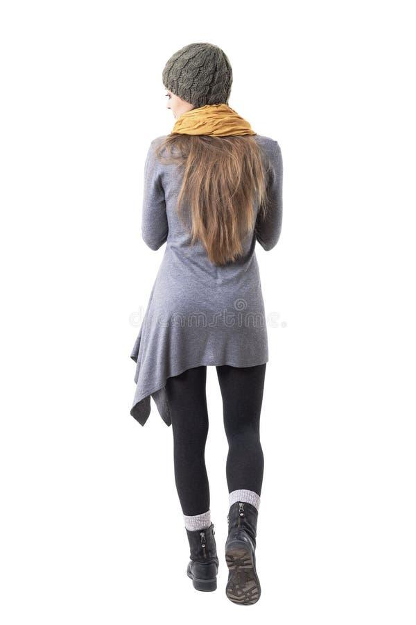 Punto di vista posteriore della ragazza unica dei pantaloni a vita bassa di stile in vestiti di inverno che si allontana tenendo  immagini stock