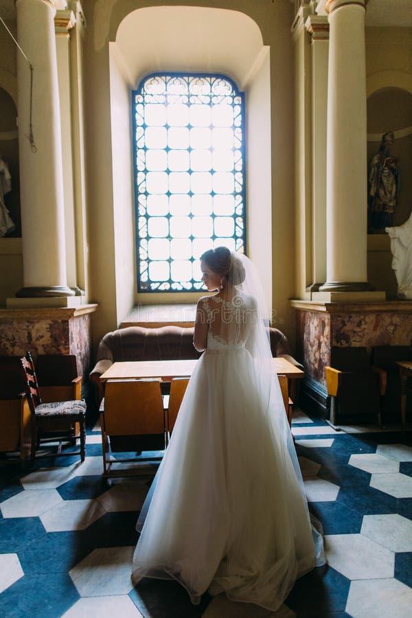Punto di vista posteriore della sposa alla moda vicino alla finestra nella chiesa fotografia stock libera da diritti