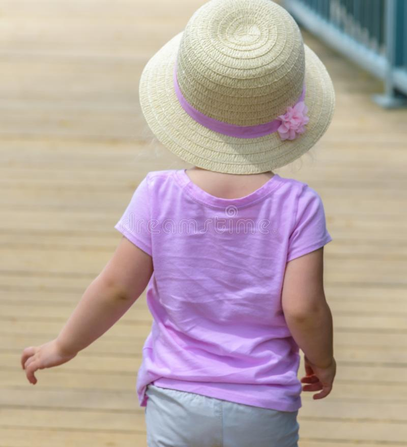 Punto di vista posteriore delle bambine in cappello del sole che camminano sul ponte fotografie stock libere da diritti