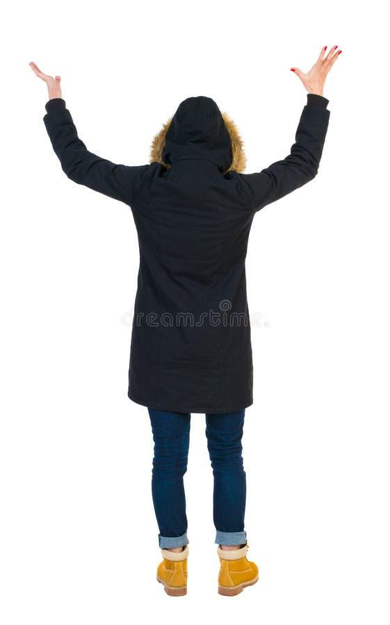 Punto di vista posteriore di bella donna in parka che esamina parete e le tenute immagini stock libere da diritti