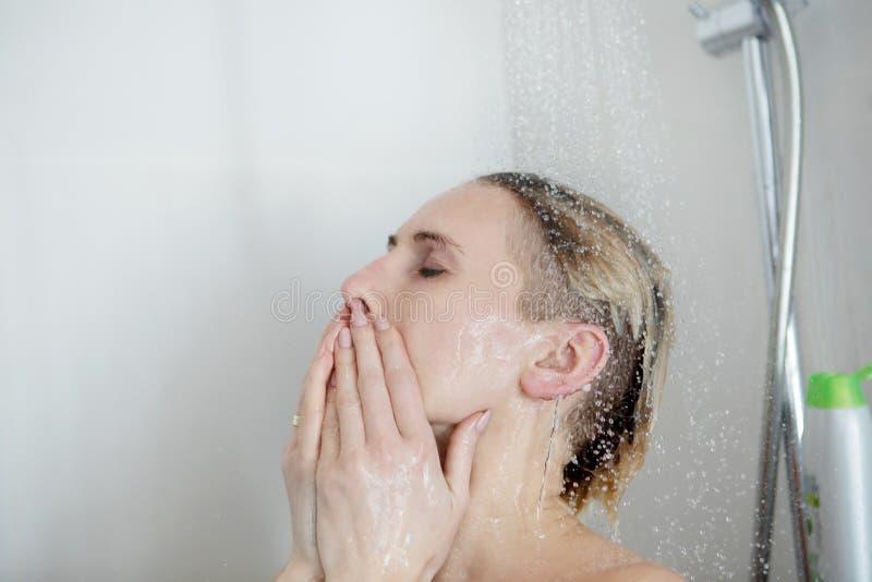 Punto di vista posteriore di bella giovane donna nuda che prende doccia fotografie stock libere da diritti