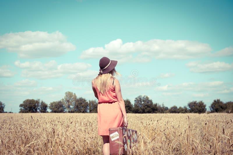 Punto di vista posteriore di bella giovane signora con la valigia della campagna del paesaggio sul fondo all'aperto fotografia stock libera da diritti