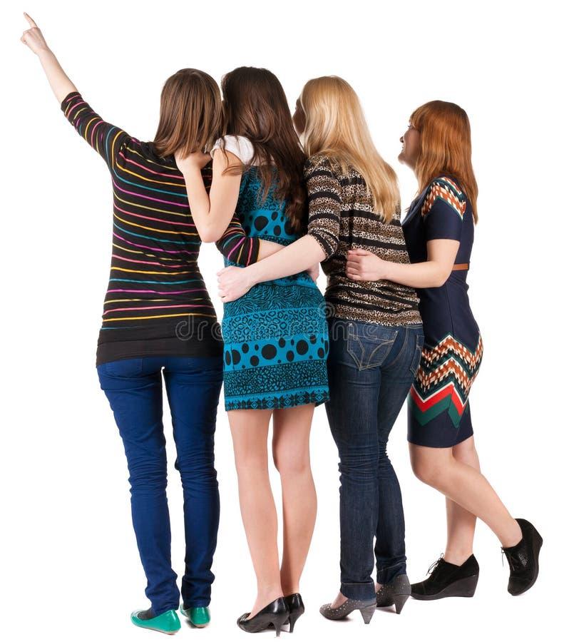 Punto di vista posteriore di belle donne del gruppo che indicano alla parete. immagini stock libere da diritti