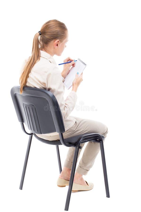 Punto di vista posteriore di giovane bella donna che si siede sulla sedia e sulle prese fotografia stock