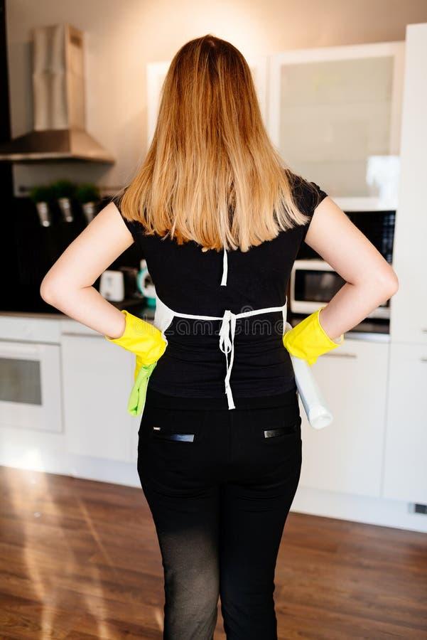 Punto di vista posteriore di giovane domestica che si prepara per pulire immagine stock