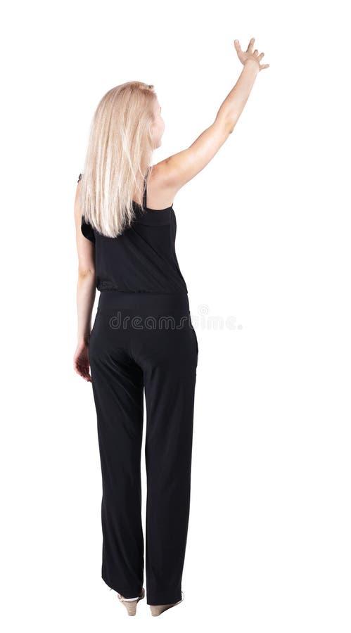 Punto di vista posteriore di giovane donna bionda che indica alla parete fotografia stock libera da diritti