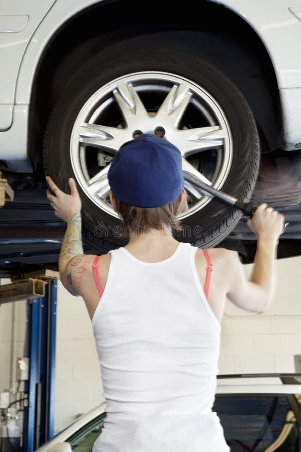 Punto di vista posteriore di giovane meccanico femminile che lavora alla gomma dell'automobile sollevata nell'officina riparazioni immagine stock