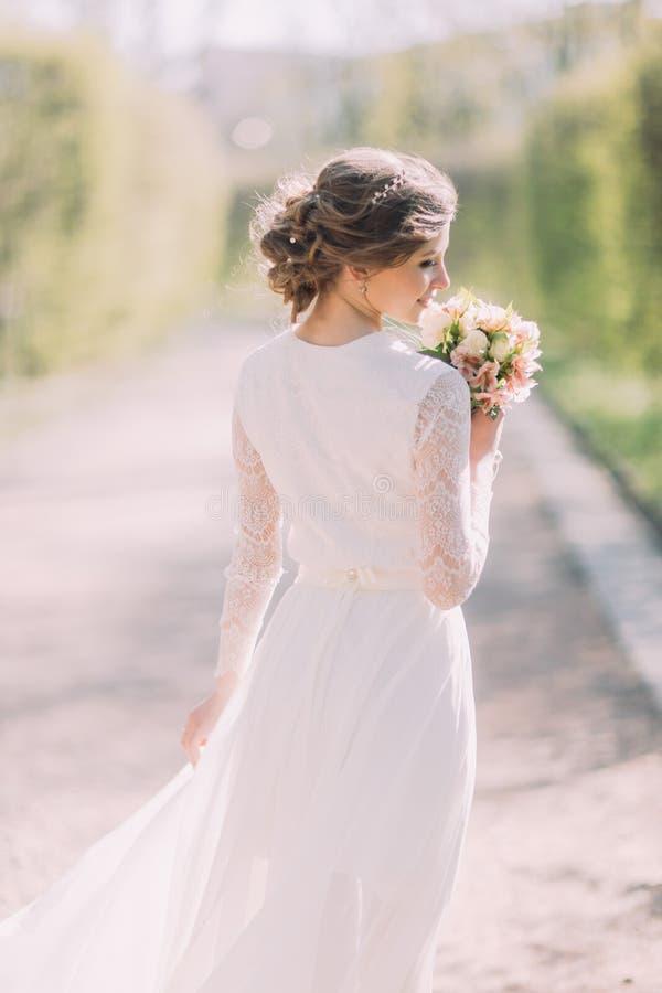 Punto di vista posteriore di giovane sposa bionda in vestito bianco che esamina mazzo nuziale all'aperto fotografia stock