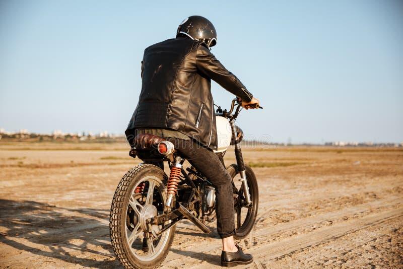 Punto di vista posteriore di giovane uomo brutale che conduce un motociclo fotografie stock libere da diritti