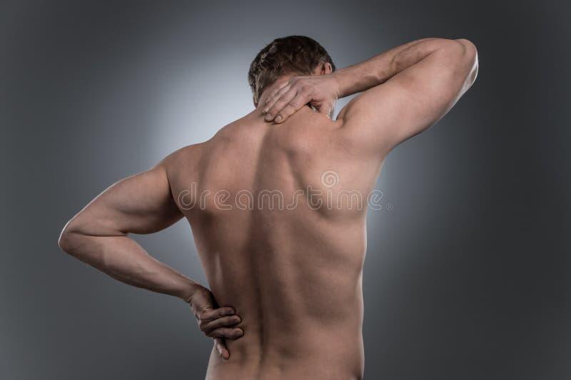 Punto di vista posteriore di giovane uomo senza camicia con dolore al collo fotografie stock libere da diritti