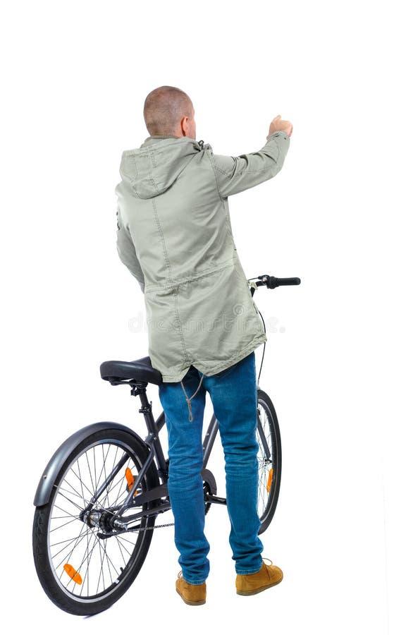 Punto di vista posteriore di un uomo con una bicicletta fotografia stock