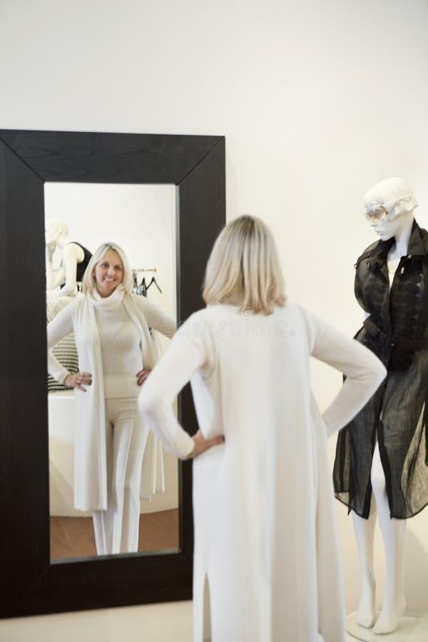 Punto di vista posteriore di una donna senior che sta con le mani sulle anche davanti allo specchio che la esamina fotografia stock
