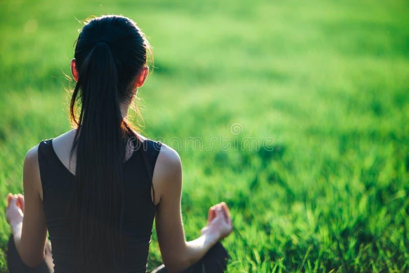 Punto di vista posteriore di giovane donna di forma fisica che medita su erba immagini stock libere da diritti