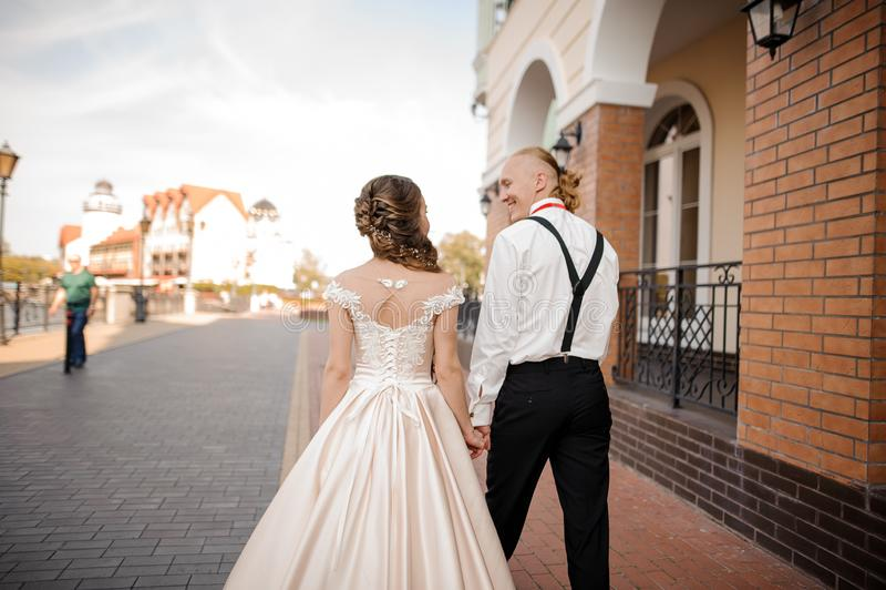 Punto di vista posteriore di giovane e coppia sposata sorridente felice che cammina nella città fotografia stock