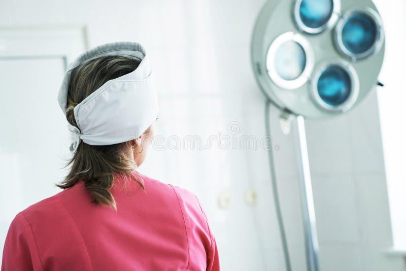 Punto di vista posteriore di un assistente femminile stanco del chirurgo che esamina finestra nella sala operatoria immagini stock