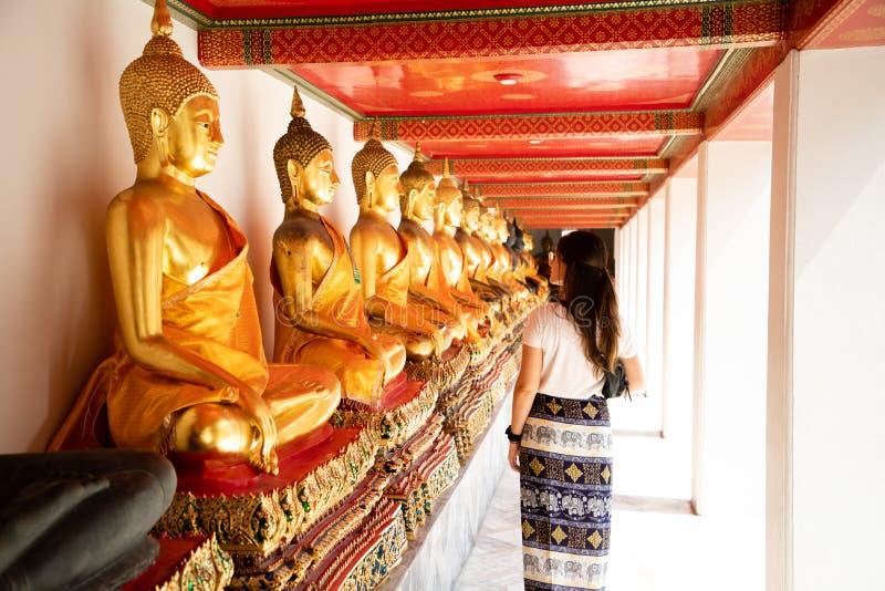 Punto di vista posteriore di un lato di camminata della donna alle statue dorate state allineate di Buddha al tempio verde smeral fotografia stock