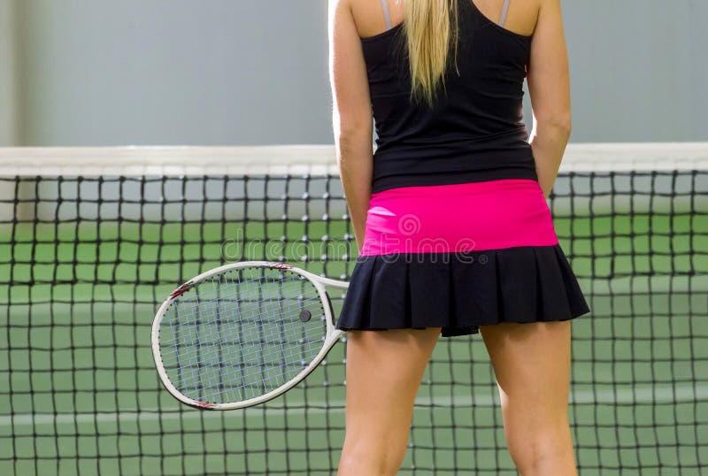 Punto di vista posteriore di un tennis femminile con una racchetta nell'azione fotografia stock libera da diritti