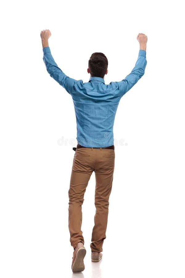 Punto di vista posteriore di un uomo casuale che celebra successo fotografia stock libera da diritti