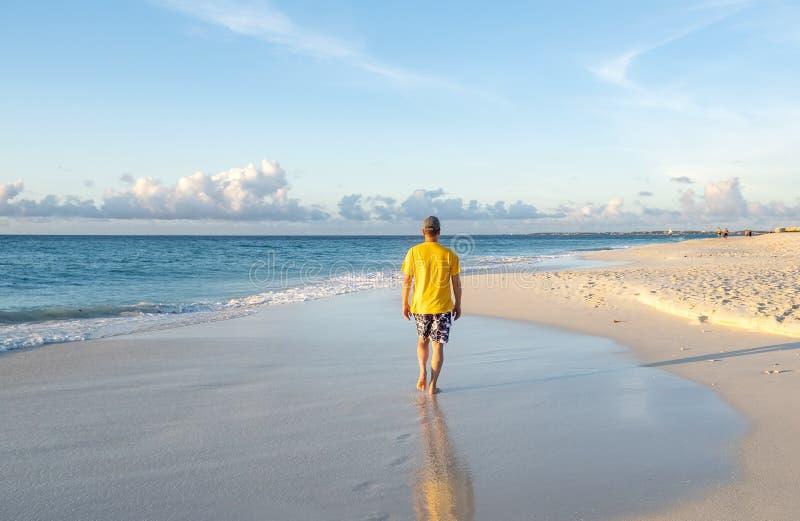 Punto di vista posteriore di un uomo che cammina su una spiaggia caraibica 2 immagine stock