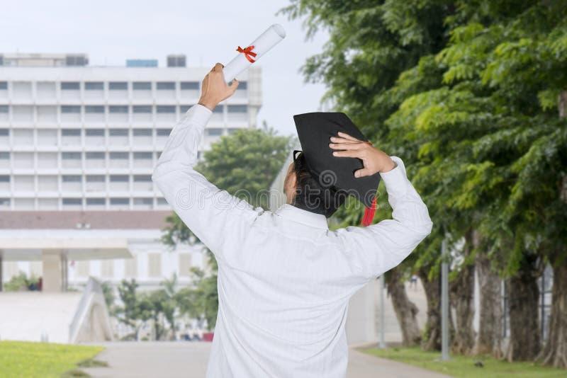 Punto di vista posteriore di un uomo che celebra la sua graduazione immagini stock libere da diritti
