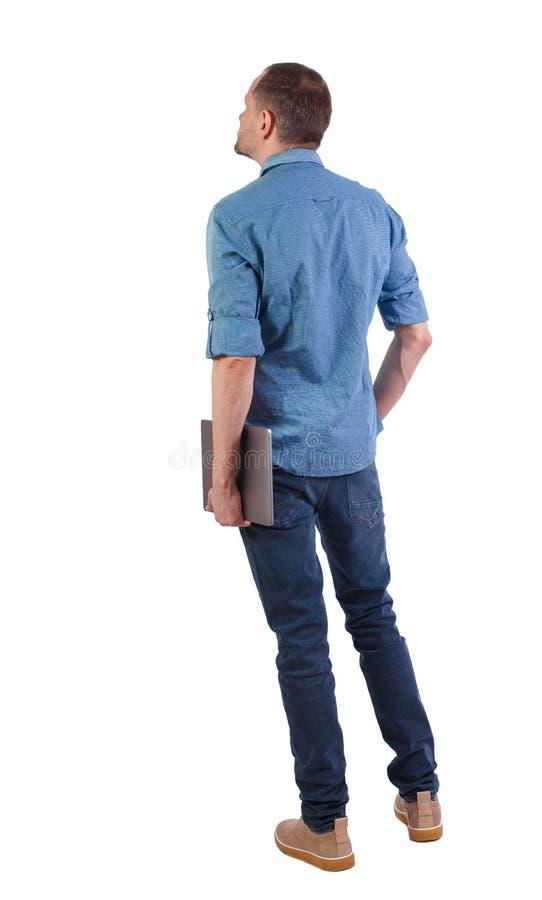 Punto di vista posteriore di un uomo che sta stando con un computer portatile immagini stock libere da diritti