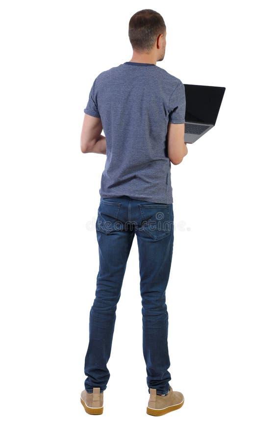 Punto di vista posteriore di un uomo che sta stando con un computer portatile fotografia stock libera da diritti