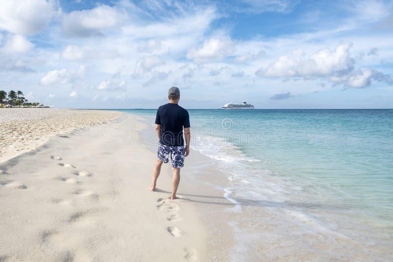 Punto di vista posteriore di un uomo che sta su una spiaggia caraibica e su una nave da crociera nella distanza immagini stock libere da diritti
