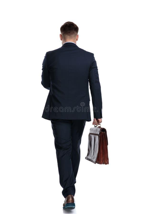 Punto di vista posteriore di un uomo d'affari motivato che tiene la sua cartella immagine stock