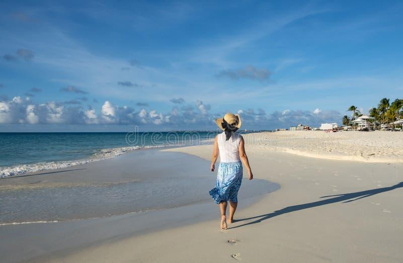Punto di vista posteriore di una donna che cammina a piedi nudi su una spiaggia caraibica 5 fotografie stock