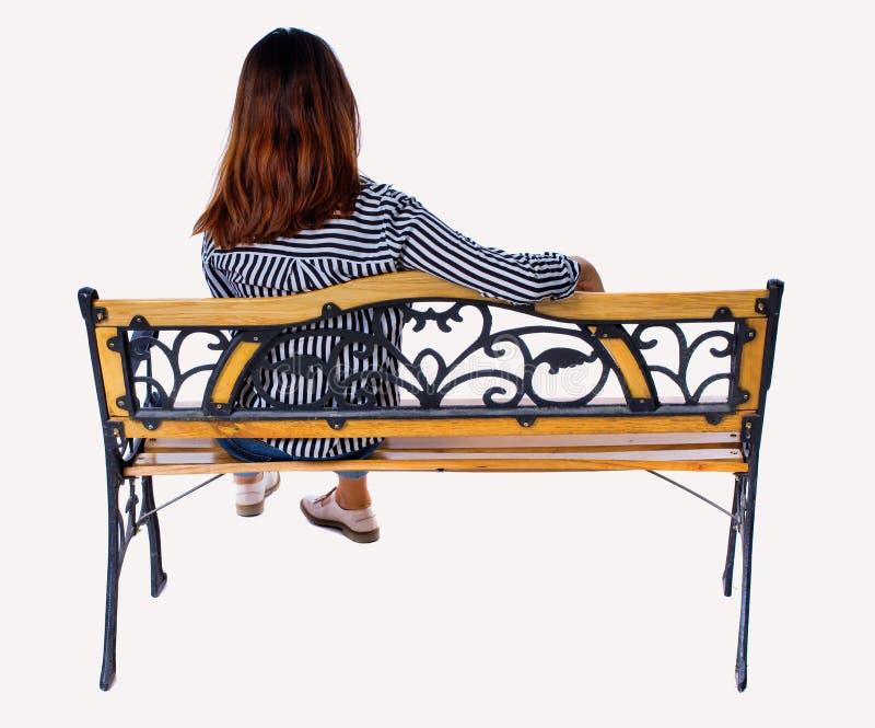 Punto di vista posteriore di una donna che si siede sul banco fotografia stock
