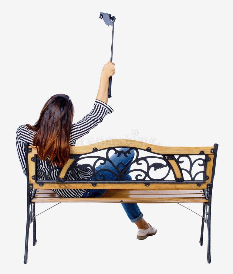 Punto di vista posteriore di una donna per fare il ritratto del bastone del selfie che si siede sul banco immagine stock