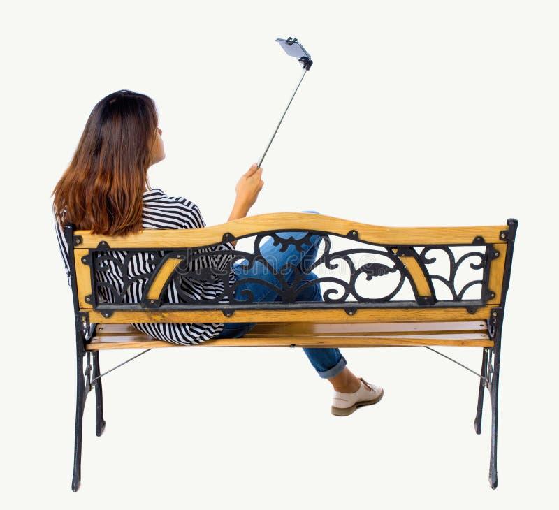 Punto di vista posteriore di una donna per fare il ritratto del bastone del selfie che si siede sul banco immagini stock