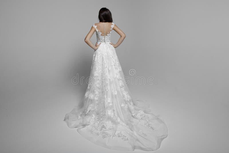 Punto di vista posteriore di una donna sensuale castana in vestito da sposa delicato bianco da principessa, isolato su un fondo b immagini stock