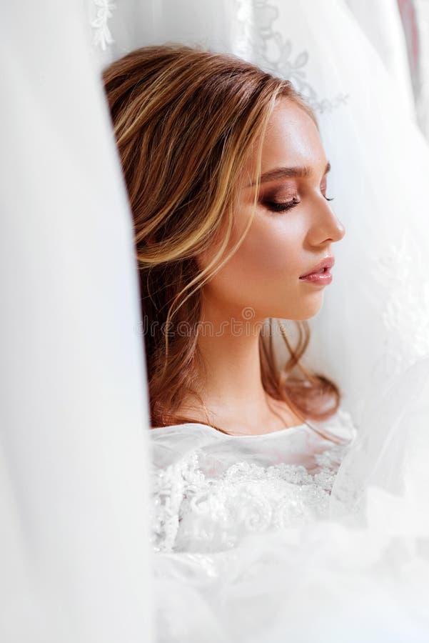 Punto di vista posteriore di una giovane donna in vestito da sposa che esamina gli abiti nuziali immagini stock